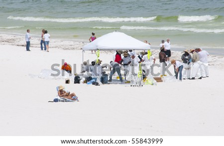 PENSACOLA BEACH - JUNE 23:  An unidentified beachgoer tries to enjoy the beach near BP oil workers on June 23, 2010 in Pensacola Beach, FL. - stock photo