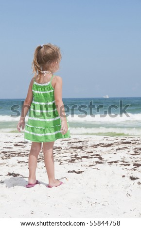 PENSACOLA BEACH - 23 JUNE: An unidentified young girl stands near oil covered sand on June 23, 2010 in Pensacola Beach, FL. - stock photo