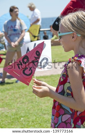 """PENSACOLA, FL - MAY 25: Protesters rally in Pensacola, FL on May 25, 2013 to show support for worldwide """"March on Monsanto"""" day to express concern over GMO (genetically modified) foods and labeling. - stock photo"""