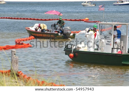 PENSACOLA - JUNE 10:  Oil spill workers in hazardous material suits collect oil-soaked debris on June 10, 2010 from the shores of Naval Air Station, Pensacola, FL. - stock photo