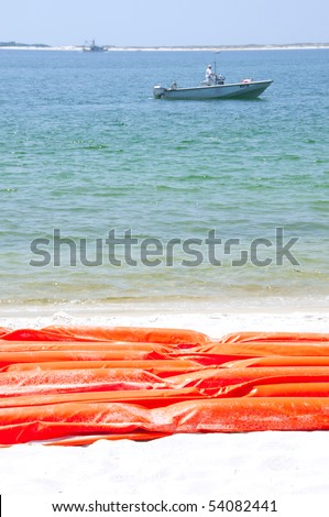 PENSACOLA - MAY 27: A boater passes near a protective oil boom as it lies along the beach area on May 27, 2010 in Pensacola, Florida. - stock photo