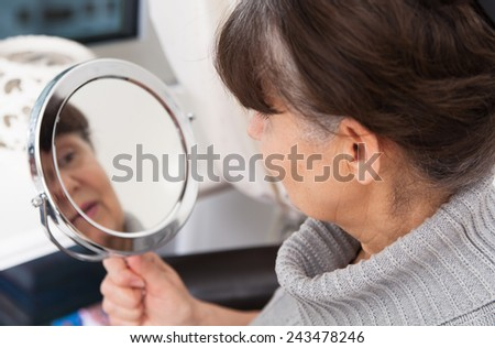 Pension age good looking woman looking in mirror  - stock photo