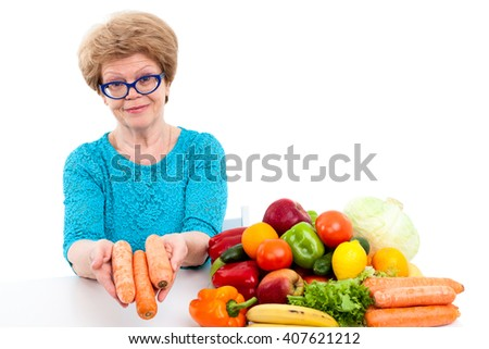 Pension age woman holding red carrots in hands, fresh fruit and vegetables on table, isolated on white background - stock photo