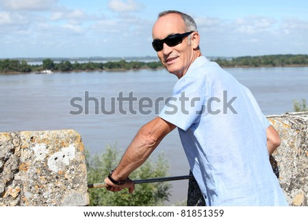 Pensioner stood by waterfront - stock photo