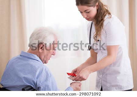 Pensioner taking his daily dose of pills - stock photo