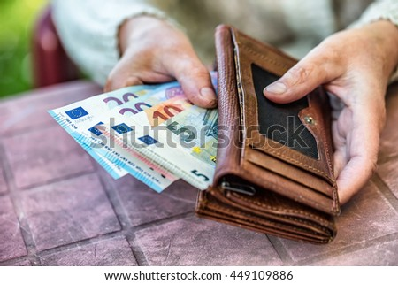 Pensioner woman holding in hands wallet with money. - stock photo