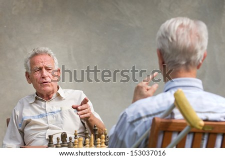 Pensioners talking and playing chess in courtyard - stock photo