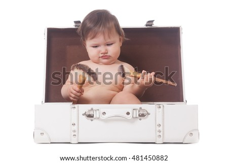 Pensive adorable girl sitting in the case with make-up brushes