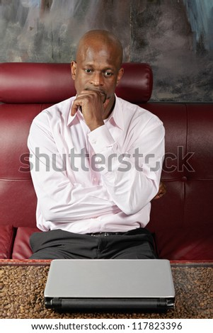 Pensive african guy in pink shirt sitting on sofa at table with closed laptop - stock photo