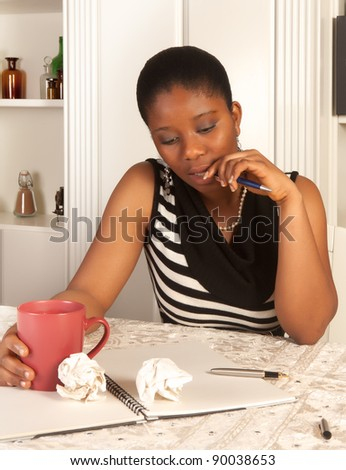 Pensive african woman writing a letter at home - stock photo