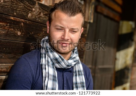 Pensive attractive man leaning against wooden wall fashion relaxing scarf