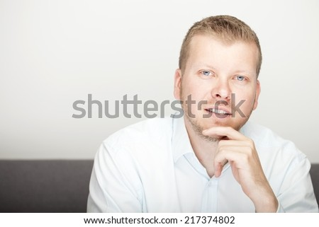 Pensive attractive young man sitting with his hand to his chin gazing thoughtfully at the camera, with copyspace - stock photo