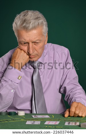 pensive beautiful aged man playing in casino - stock photo