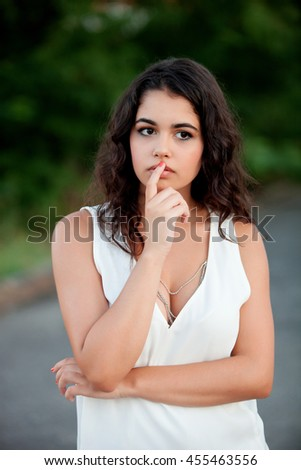 Pensive beautiful brunette girl relaxing in the park with many plants of background - stock photo