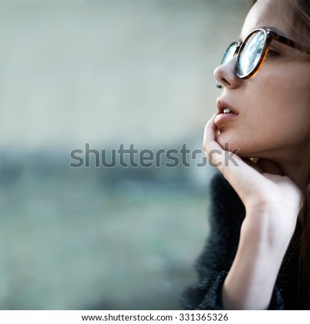 Pensive beautiful young woman in stylish sunglasses closeup