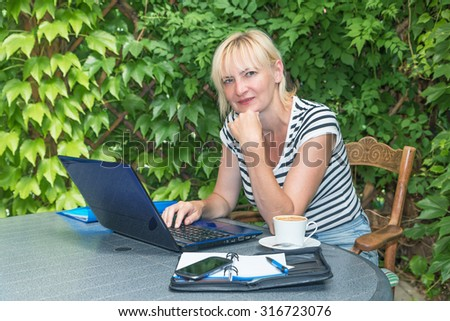 Pensive blonde middle aged woman is sitting outdoors on the terrace  with open notebook, diary and smart phone on the table and is looking to the camera. Woman is supporting her chin by hand.  - stock photo