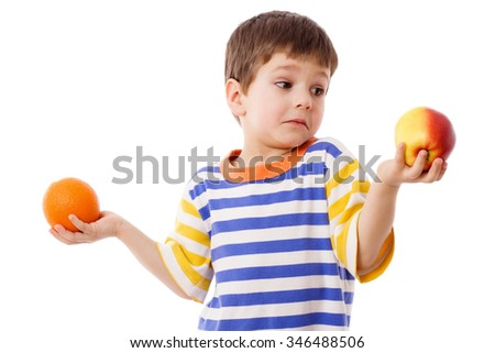 Pensive boy holds a orange and red apple, isolated on white - stock photo