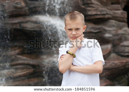 Pensive boy on a background of a waterfall.