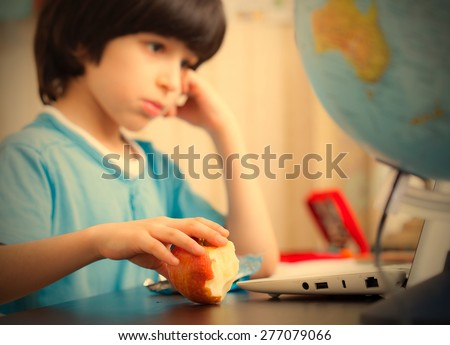 pensive boy sitting at a table with a laptop and eating apple. focus on fruit. instagram image retro style - stock photo
