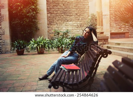 Pensive brunette hair woman sitting in beautiful spanish patio bench looking into the distance, charming lovely woman enjoying her leisure time outdoors, flare light, cross process - stock photo