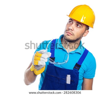 Pensive builder looking up, isolated on white background. Construction worker in hardhat holding protective goggles