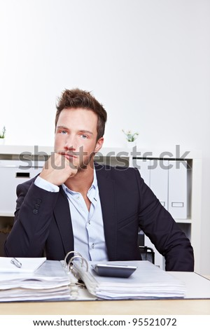 Pensive business man with files sitting at desk in office - stock photo