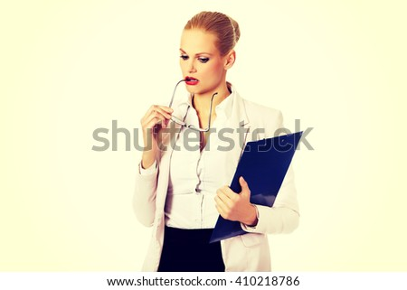 Pensive business woman holding a clipboard and glasses - stock photo