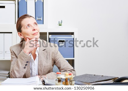 Pensive business woman sitting in her office at the desk - stock photo