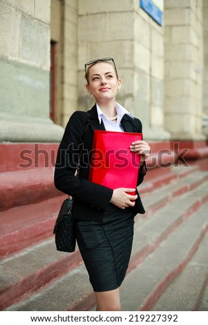 Pensive business woman with a folder outdoors - stock photo