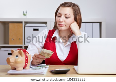 Pensive business woman with Euro money and piggy bank in office - stock photo
