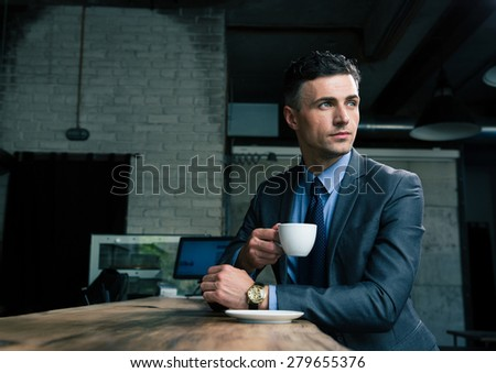 Pensive businessman drinking coffee in cafe and looking away - stock photo