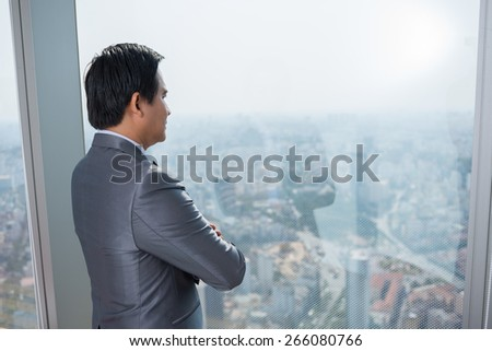 Pensive businessman looking through the window, view from the back - stock photo