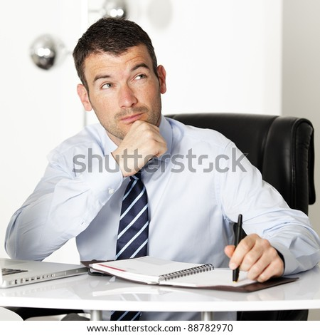 pensive businessman looking up in office with pen - stock photo