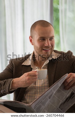 Pensive businessman reading a newspaper in cafe