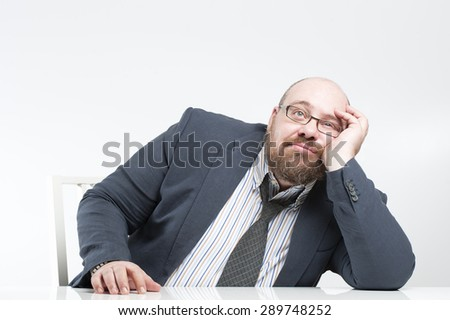 Pensive businessman sitting at the table.
