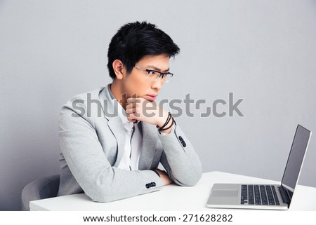 Pensive businessman sitting at the table with laptop over gray background and looking on laptop - stock photo