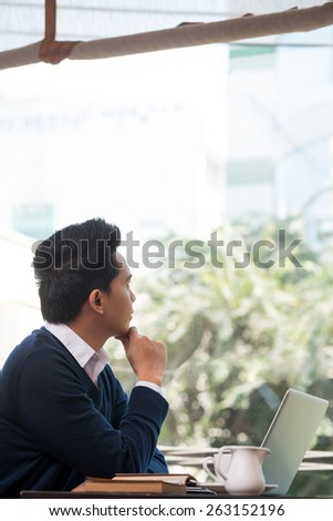 Pensive businessman sitting in the cafe and looking through the window - stock photo