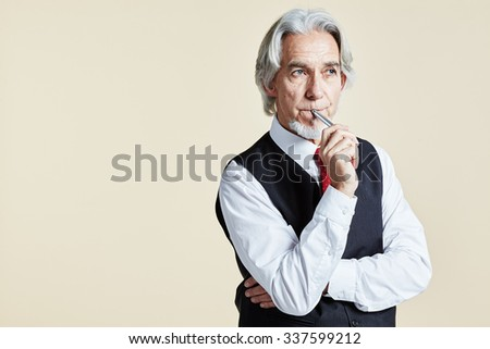 Pensive businessman with arms crossed and pen at lips