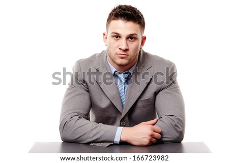 Pensive businessman with hands resting on the table, isolated over white background - stock photo