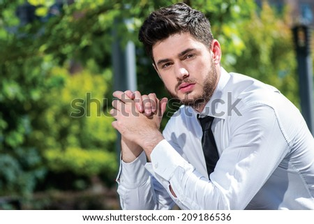 Pensive businessman! Young businessman with a beard sitting on a bench and folded his hands looking at the camera. Successful businessman in formal attire. - stock photo