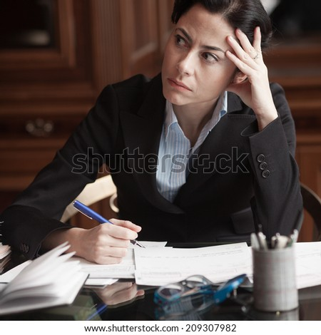 Pensive businesswoman on her desktop - stock photo