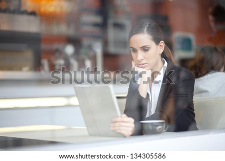 Pensive businesswoman reading an article on tablet computer in a pub - stock photo
