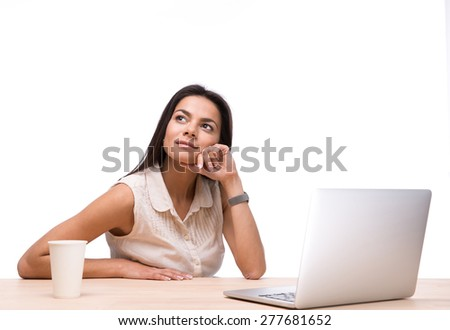 Pensive businesswoman sitting at the table with laptop and looking up over white background - stock photo