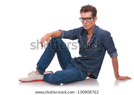 pensive casual young man is looking with a deep look at the camera while sitting relaxed on the floor. isolated on white - stock photo