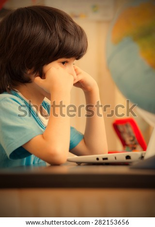 pensive child sitting at a table with a laptop. instagram image retro style - stock photo