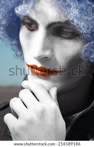 Pensive clown with blue wig. Vertical colorful portrait - stock photo