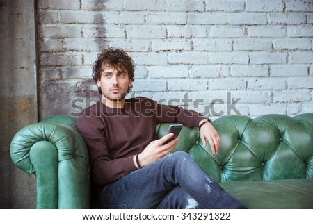 Pensive curly thoughtful attractive young handsome man in brown sweetshirt and jeans sitting on green leather sofa hoding cellphone - stock photo