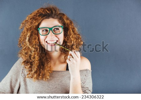 Pensive Curly Young Woman on Gray Background - stock photo