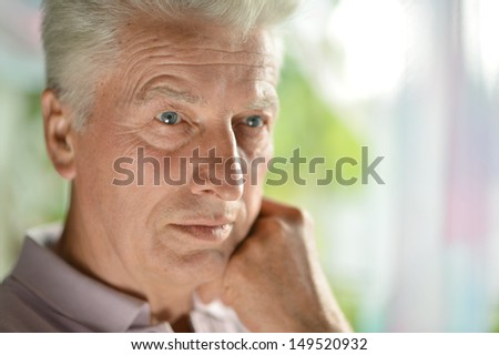 Pensive elderly man at home - stock photo