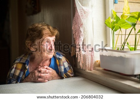 Pensive elderly woman looking out the window. - stock photo